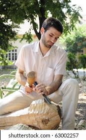 young man sculpting wood material