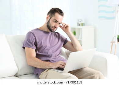 Young man searching information using laptop at home