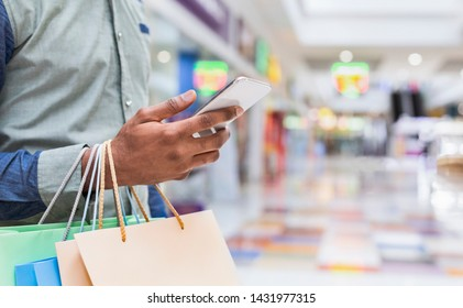 Young man searching new clothes through cellphone online in shopping mall, panorama, copy space