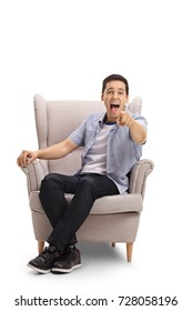 Young man seated in an armchair pointing at the camera and laughing isolated on white background
