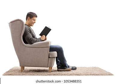 Young man seated in an armchair reading a book isolated on white background