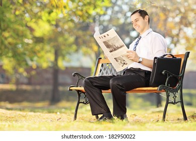 Young man seated on a wooden bench reading a newspaper in a park on a sunny day