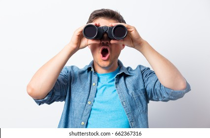 Young man seeking with binocular something on white background