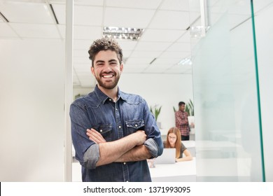 Young man as a self-confident start-up business founder in front of the coworking office