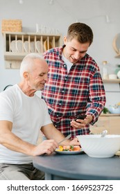 Young man and senior father using phone in the kitchen