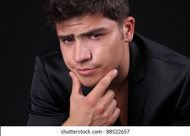 Young man with a serious look over black background
