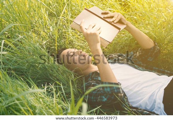young man, serious student (male) hand holding book and reading on background of a meadow
