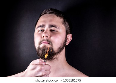 Young man set fire to his beard with a cigarette lighter. Smoke from arson beard. Beard on fire.