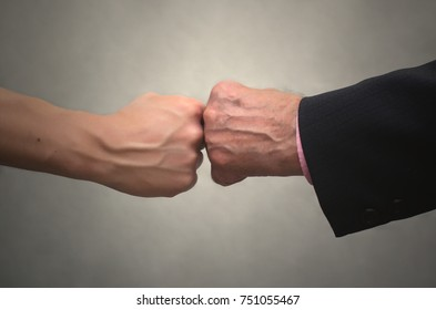 A young man shakes hands with an elderly person in suit isolated on white background. Assignee. The son shakes his father's hand.