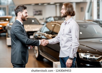 Young man shaking hand with professional salesperson having a deal in the showroom with luxury cars on the background