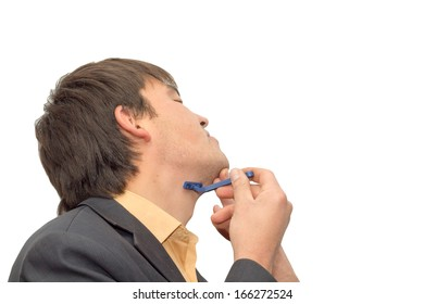 Young man shaves his beard himself
