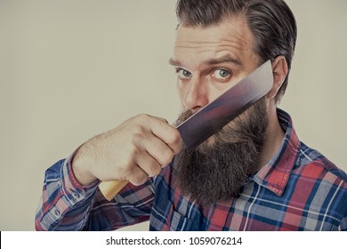 young man shaving his beard with butcher knife