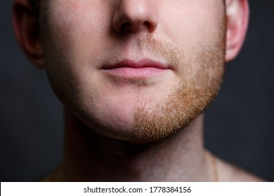 Young man shaving his beard. He shaved off half the bristles against a gray background. Male face care. Shaving bristles. The difference between skin without hair and with a mustache