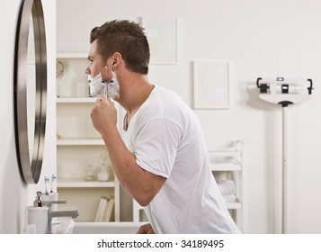 A young man is shaving his face in front of the bathroom mirror.  He is looking away from the camera.  Horizontally framed shot.