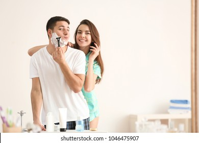 Young man shaving and his girlfriend in bathroom