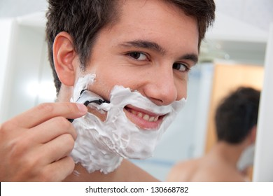 young man shaving with razor and shaving cream in bathroom