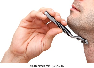 Young man shaving with a razorblade