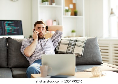Young man in shirt and blue jeans sitting on sofa in front of laptop while talking to someone on smartphone