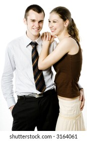 A young man in shirt and tie with his girlfriend in casual clothing on white background