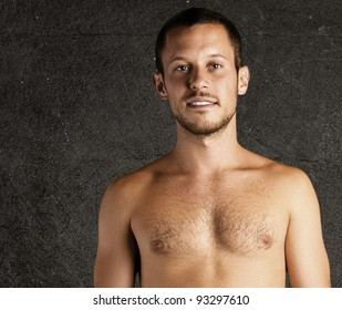young man shirtless against a grunge background