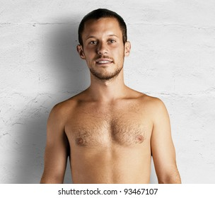 young man shirtless against a white wall