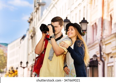 Young man shooting with camera and girl near