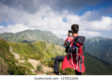 Young man is shooting a photo in the mountain