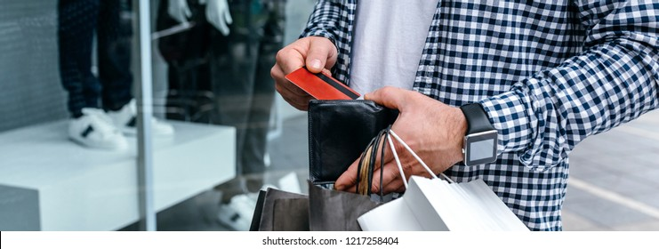 Young man with shopping bags taking out credit card from wallet