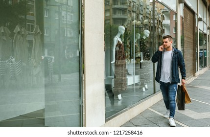 Young man with shopping bags walking in front of a clothing store