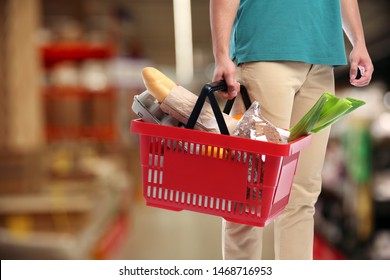 Young man with shopping basket full of different products in supermarket, closeup. Space for text