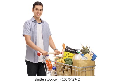 Young man with a shopping cart filled with groceries isolated on white background