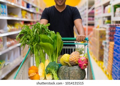 Young man shopping fresh fruit and vegetables at supermarket.