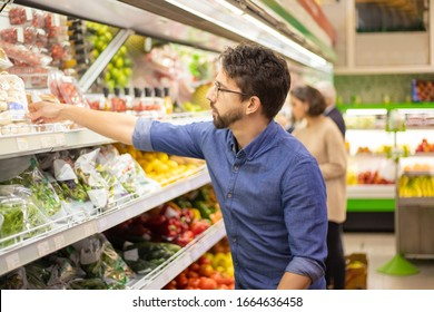 Young man shopping in grocery store. Side view of focused man and woman holding shopping baskets and choosing fresh fruits and vegetables in supermarket. Shopping concept