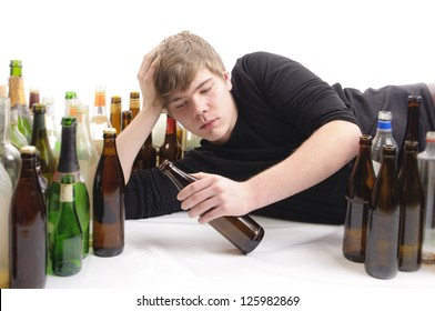 Young man with short blond hair lying on the floor and is surrounded by many empty beer and liquor bottles, isolated against white background.