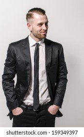 Young man with short hair and stubble wears a dark suit and a narrow tie. He has his hands casually in his pockets and looks into the distance. Isolated against a gray background.