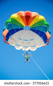 a young man in shorts is flying on a parachute on the blue sky background