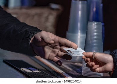 Young man show valid ID to buy alcohol and cigarettes in pub photographed with shallow depth of field