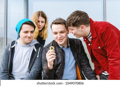 young man showing bitcoin coin to his intrigued group of friends, cryptocurrency hype concept