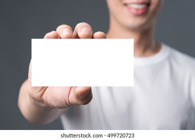 Young man showing blank white business card