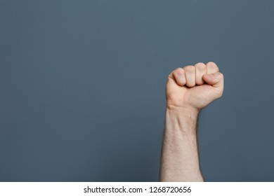 Young man showing clenched fist on color background. Space for text