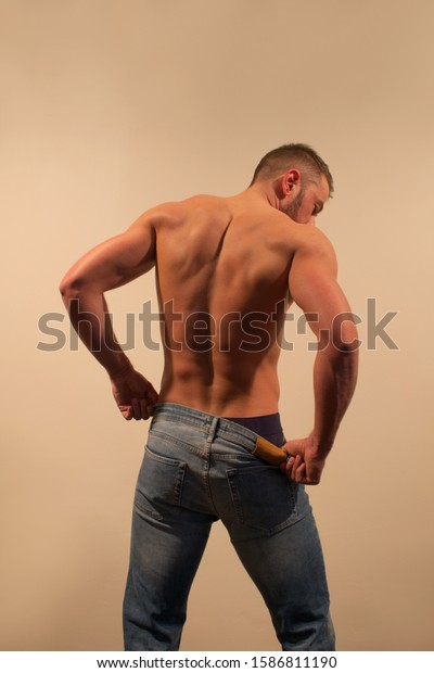 Young man showing his muscular back. Sexy muscle man in blue jeans isolated on light background. Back view.
