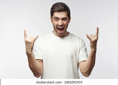 Young man showing rock sign with his fingers as if listening to favourite music, isolated on white background