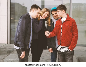 young man showing something on his mobile phone to a group of friends - urban teenage lifestyle