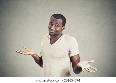 Young man shrugging shoulders who cares so what I don't know gesture isolated on grey wall background. Body language