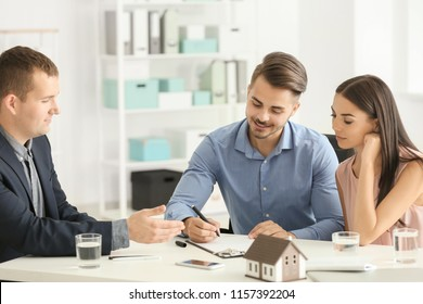 Young man signing a contract for buying house in office of estate agent