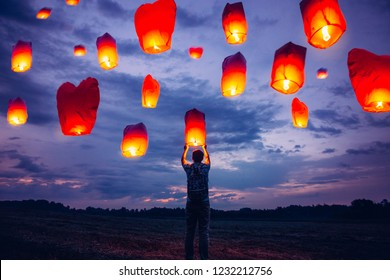 Young man silhouette  releases sky lanterns in the sunset purple sky.  A large group of chinese flying lanterns, red colours, heart shaped lantern