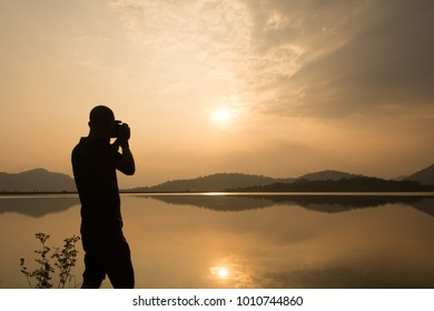 Young man silhouette taking photos about landscape outdoor