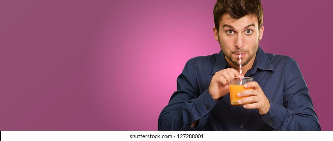 Young Man Sipping Juice Through Straw Isolated On Pink Background