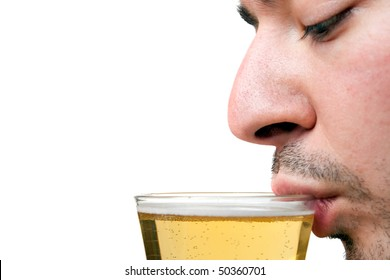 A young man sipping a tall glass of beer isolated over white.  Shallow depth of field with sharp focus on the lip and beer.