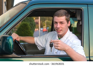 A young man sit in a car and hold the car key